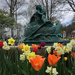 statue with spring flowers by Mia Lisa Anderson